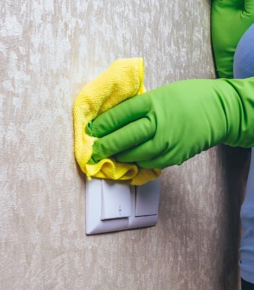 Personal de limpieza limpiando las llaves de luz después de una reforma de hogar.