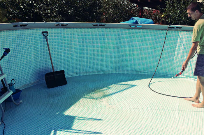 Persona limpiando una piscina desmontable antes de guardar