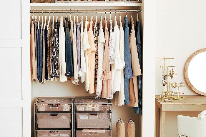 Armario pequeño organizado con la ropa colocada por tipos