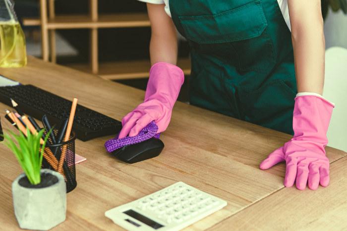 Persona limpiando y ordenando el puesto de trabajo