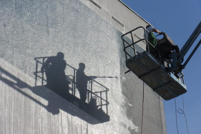 Operarios limpiando una fachada con chorro de arena